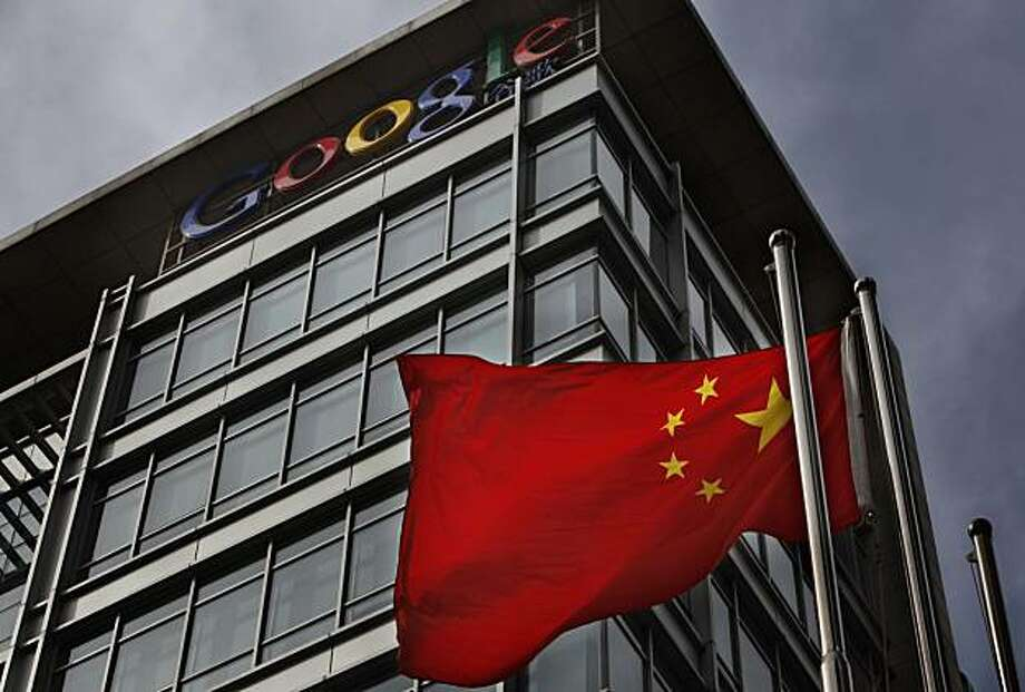A Chinese flag blows in the air below the Google logo outside the Google China headquarters in Beijing Thursday, March 25, 2010. While Google's decision to move its Chinese search engine offshore challenging China's online censorship laws win praise in the U.S. and other countries, it's threatening to turn the company into a pariah in China. Photo: Gemunu Amarasinghe, Associated Press