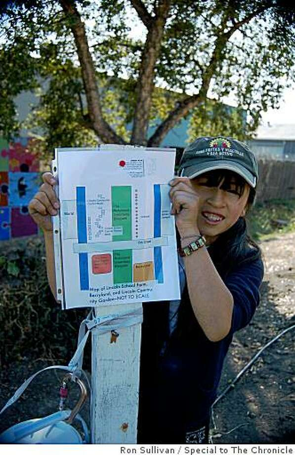 "Briana Orozco, a two-year veteran in Lincoln School's garden program, shows us the garden map. Briana is in charge of her group's supplies: ""I own all the pencils and plant tags!""Briana's (NB one ""n"") last initial is ""O""  for Orozco and Park Guthrie is checking about school policy re: using last names. Last place he taught in had policy against it but he thinks that was because most of them were minors on probation. Photo: Ron Sullivan, Special To The Chronicle"