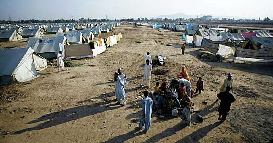 Pakistani people from the Bajur tribal region collect water from a water point at the Katcha Garhi camp in Peshawar, Pakistan, Sunday, Oct. 19, 2008. Refugees fleeing a Pakistani offensive against militants said the army is bombing their homes, killing women, children and livestock. Nearly 200,000 people have fled the fighting in Bajur regency to camps in Afghanistan and Pakistan.  (AP Photo/Emilio Morenatti) Photo: Emilio Morenatti, AP