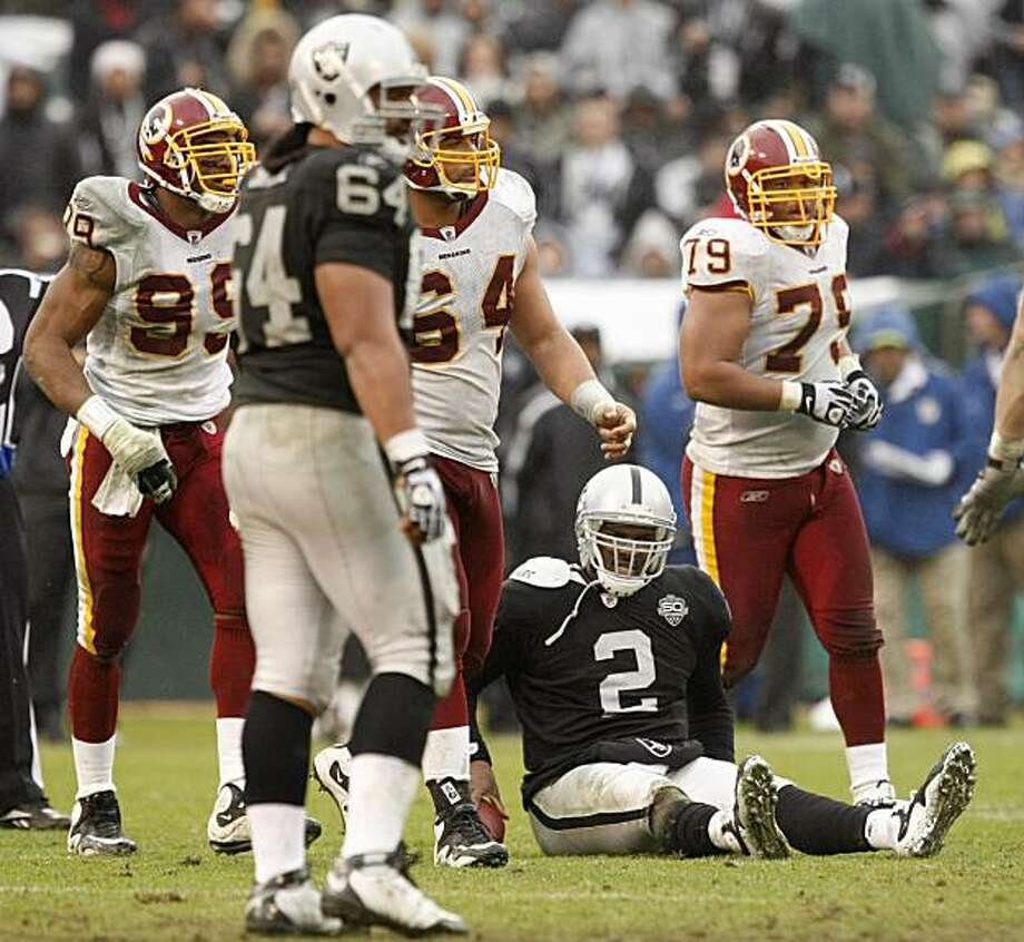 Oakland Raiders quarterback JaMarcus Russell (2) sits on the ground beneath Washington Redskins defensive end Andre Carter (99), defensive tackle Kedric Golston (64), and defensive tackle Lorenzo Alexander (79) after being sacked during the third quarter of an NFL football game in Oakland, Calif., Sunday, Dec. 13, 2009. The Redskins won 34-13. (AP Photo/Marcio Jose Sanchez) Photo: Marcio Jose Sanchez, AP