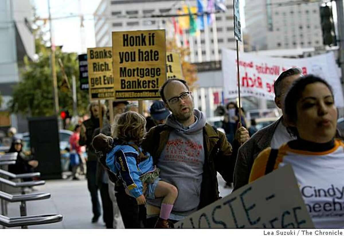 Brian Miller of San Francisco holds his daughter, Franny Mitchler, 2, while walking with protesters on Howard and 4th Streets outside of the MBA�s 95th Annual Convention & Expo at Moscone West on Monday October, 20 2008 in San Francisco, Calif.