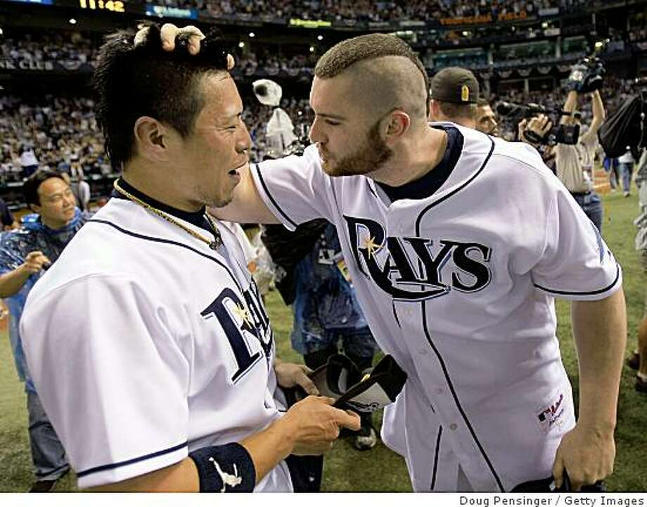 ST PETERSBURG, FL - OCTOBER 19:  Akinori Iwamura #1 and Jonny Gomes #31 of the Tampa Bay Rays celebrate after defeating the Boston Red Sox in game seven of the American League Championship Series during the 2008 MLB playoffs on October 19, 2008 at Tropicana Field in St Petersburg, Florida.  The Rays defeated the Red Sox 3-1 to win the series 4-3.  (Photo by Doug Pensinger/Getty Images) Photo: Getty Images