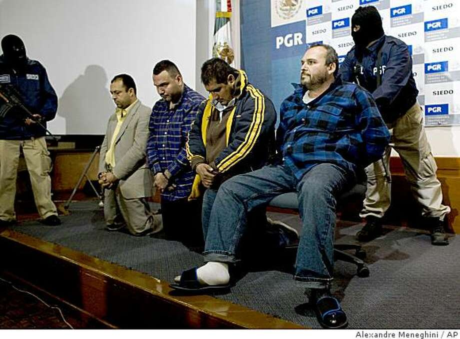 """A man identified by Mexico's Attorney General's office as Jesus Zambada Garcia, known as Jesus """"The King"""" Zambada, sitting right, one of the top four leaders of the Sinaloa drug cartel, is presented to the media along with three other alleged Sinaloa cartel members, left of Garcia, in Mexico City, Wednesday, Oct. 22, 2008. A total of 16 Sinaloa cartel members were arrested Monday, including Garcia, after a gun battle with police, according to prosecutors. (AP Photo/Alexandre Meneghini) Photo: Alexandre Meneghini, AP"""