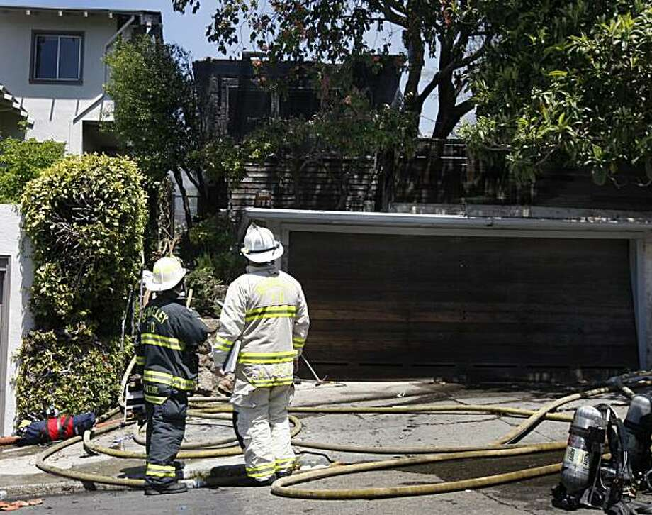 Fire officials inspect the damage after a three-alarm fire destroyed one home and damaged two others on San Luis Road  in Berkeley, Calif., on Thursday, May 13, 2010. No one was reported injured and cause of the fire is under investigation. Photo: Paul Chinn, The Chronicle