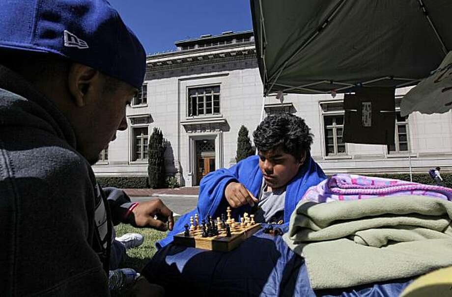 UC Berkeley students, Ismael Armendariz, (left) and Nestor Espinoza, pass the time playing chess as they join 22 other hunger strikers who are camped out in front of California Hall on the UC Berkeley campus, in Berkeley, Calif. on Thursday May 06, 2010, demanding that UC President Mark Yudof and UC chancellors denounce the Arizona legislation, the hunger strikers called racist, which gives law enforcement broad powers to detain people they suspect of being in the country illegally. Photo: Michael Macor, The Chronicle