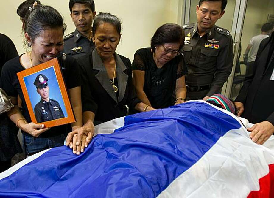 BANGKOK, THAILAND - MAY 08:  Relatives of Pol Cpl Karnnuphat Lertchanpen, a traffic police officer mourn his death at the Institute of Forensic Police General Hospital on May 8, 2010 in Bangkok, Thailand. Two Thai policemen have been killed in two attacksnear anti-government protest 'Red Shirt' site in the shopping district of Bangkok, which may put the government reconciliation attempt at risk. Prime Minister Abhisit Vejjajiva vows to dissolve Parliament between September 15 and 30 to end Thailand's eight weeks of political crisis but for now the red shirts say they will stay on the streets. The anti-government protests that have closed much of central Bangkok's commercial district. Photo: Athit Perawongmetha, Getty Images