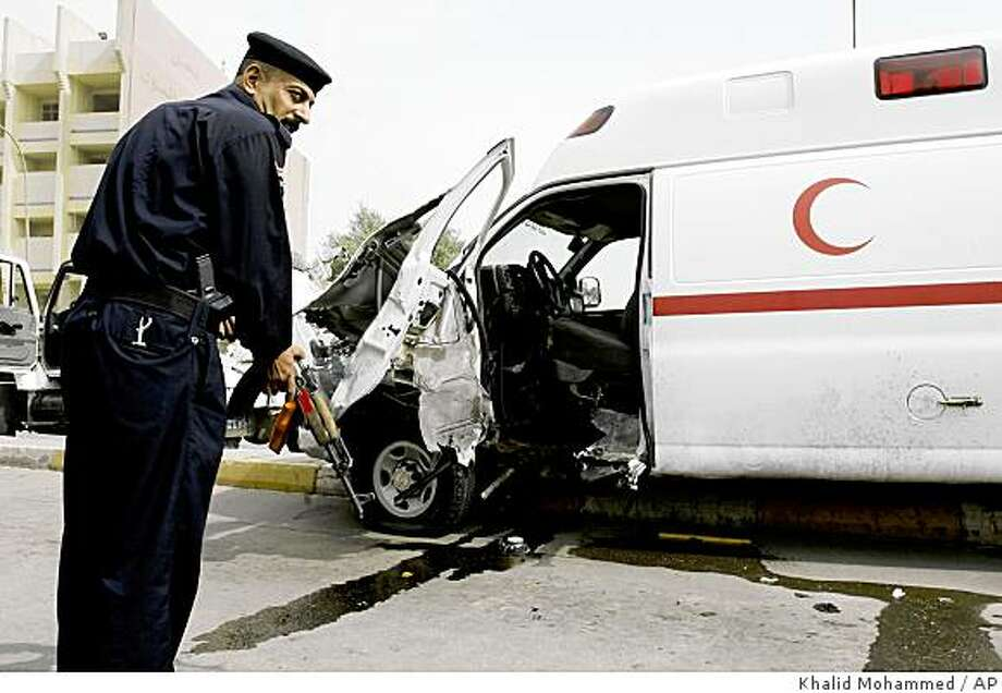 An Iraqi Policeman stands guard at the scene were a roadside bomb struck an ambulance in al Nidhal Street central Baghdad, on Wednesday, Oct. 22, 2008. The ambulance which was carrying a patient with heart problems, with two companions, was hit by a roadside bomb causing the death of the patient and wounding three others including the driver who lost one of his legs, police said. (AP Photo/ Khalid Mohammed) Photo: Khalid Mohammed, AP