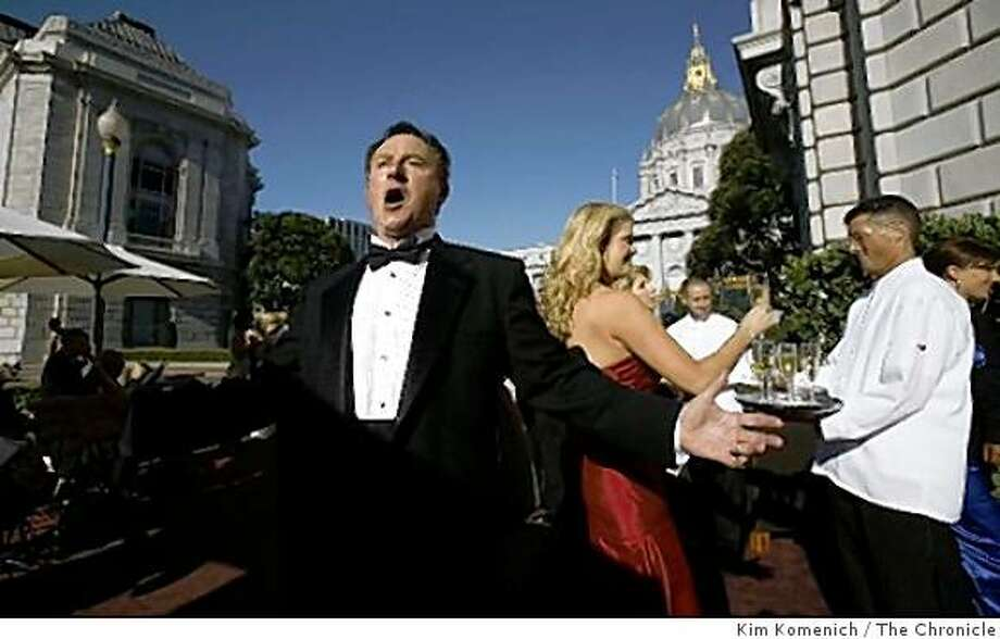 Tenor Peter Girardot serenades guests as they arrive at War Memorial Opera House in San Francisco, Calif., on Sept. 5, 2008. Photo: Kim Komenich, The Chronicle