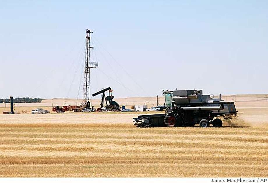 **APN ADVANCE FOR SUNDAY OCT. 19** A  combine cuts durum near an oil well on Aug. 19, 2008, in Tioga, N.D. The first producing oil in North Dakota was drilled a mile from here in 1951, spurring an oil frenzy that has lasted six decades throughout the Williston Basin. (AP Photo/James MacPherson). Photo: James MacPherson, AP