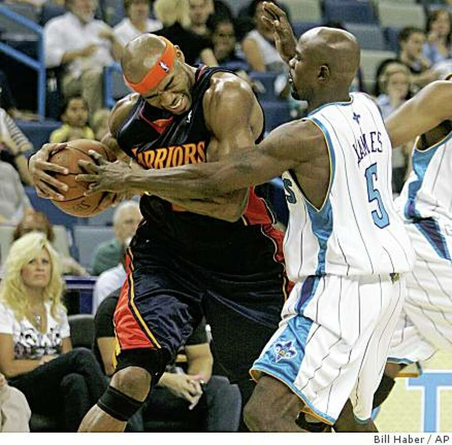 Golden State's Corey Maggette (50) keeps the ball away from New Orleans Hornets Mike James (5) in the first half of an NBA preseason basketball game in New Orleans, Sunday, Oct. 5, 2008.  (AP Photo/Bill Haber) Photo: Bill Haber, AP