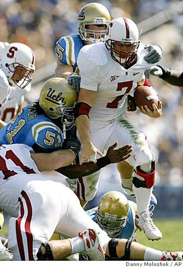 Stanford running back Toby Gerhart (7) runs the ball as UCLA's Reggie Carter (51) and Korey Bosworth, rear, attempt to tackle him during an NCAA college football game on Saturday, Oct. 18, 2008 in Pasadena, Calif. (AP Photo/Danny Moloshok) Photo: Danny Moloshok, AP