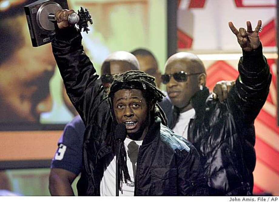 Lil Wayne, left, holds up his Lyricist of the Year award during the BET Hip Hop Awards '08, Saturday Oct. 18, 2008, in Atlanta. (AP Photo/John Amis) Photo: John Amis, File, AP