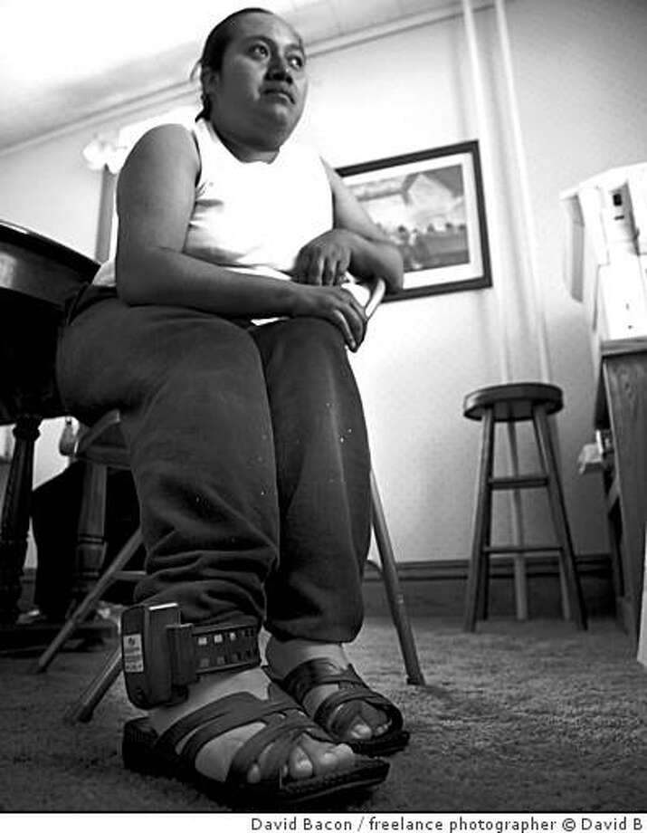 An immigrant caught up in the Postville, Iowa, meat packing raids wears a prison tracking ankle bracelet. Increasingly, illegal immigrants are herded en masse into federal courts, found guilty of entering the country illegally and imprisoned. In the past, immigrants typically were deported. dnbpostville08.jpg  POSTVILLE, IOWA - 18JULY08 - Anacleta Tajtaj, a Guatemalan immigrant, was arrested in an immigration raid at the Agriprocessors meatpacking plant in Postville.  The raid was the largest workplace raid in a single worksite in recent history.  Tajtaj was released to care for her son Edgar, but now has to wear an ankle bracelet to monitor her movements.  She cannot work or travel, and has been waiting for weeks for a hearing which would result in her deportation.Copyright David Bacon Photo: David Bacon, Freelance Photographer � David B