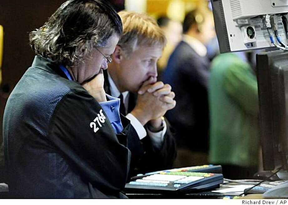 A pair of specialists work at their post on the floor of the New York Stock Exchange, Wednesday Oct. 22, 2008. Wall Street tumbled again Wednesday as investors worried that the global economy is poised to weaken even as parts of the credit market slowly show signs of recovery. The major indexes fell more than 4 percent, including the Dow Jones industrial average, which fell 515 points. (AP Photo/Richard Drew) Photo: Richard Drew, AP