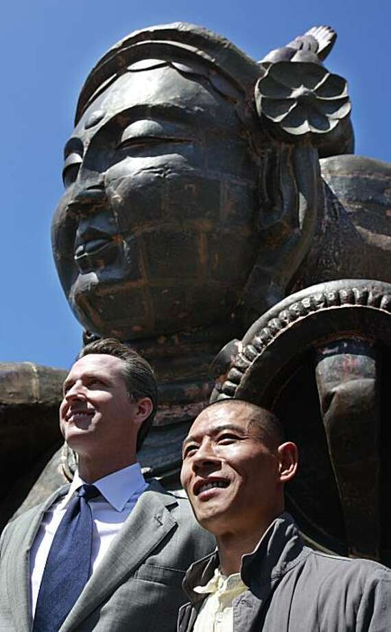 "Shanghai artist Zhang Huan, right, and San Francisco Mayor Gavin Newsom, left, smile in front of the sculpture ""Three Heads Six Arts"" during a dedication ceremony in front of San Francisco City Hall in San Francisco, Wednesday, May 12, 2010. The art depicts fragmented Buddhist statues based on both Chinese mythology and Tibetan Buddhist iconography. Photo: Paul Sakuma, AP"