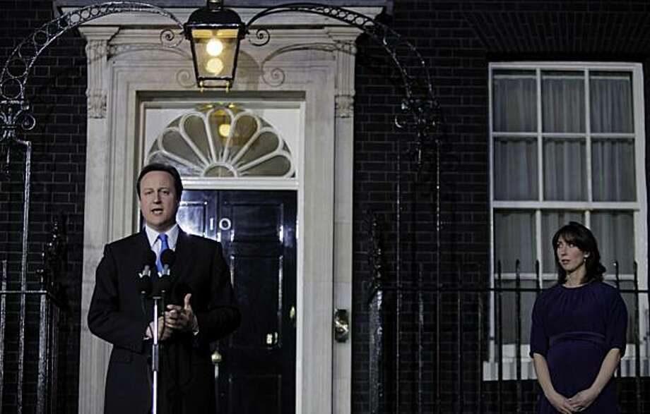Britain's new Prime Minister David Cameron, left, accompanied by his wife Samantha, right, makes a statement as he arrives at his official residence at No.10 Downing Street in central London, Tuesday May 11, 2010. (AP Photo/Lefteris Pitarakis) Photo: Lefteris Pitarakis, ASSOCIATED PRESS