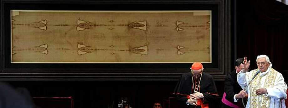 """TOPSHOTS Pope Benedict XVI (R) blesses the audience in front of the Shroud in the Turin cathedral on May 2, 2010. Pope Benedict XVI will bow before the Shroud of Turin, the object of both bafflement and veneration believed by many to be the burial cloth of Jesus Christ. """"It will be a propitious occasion to contemplate this mysterious visage that speaks silently to the heart of men, inviting them to recognise the face of God,"""" Benedict said in 2008 as he announced the planned new exposition of the mysterious cloth. The 83-year-old pontiff, in his one day visit in Turin, will celebrate an open-air mass in Piazza San Carlo next to the Turin Cathedral housing the shroud, meetings with youths and a visit to a centre for severely handicapped people.    TOPSHO Photo: Vincenzo Pinto, AFP/Getty Images"""
