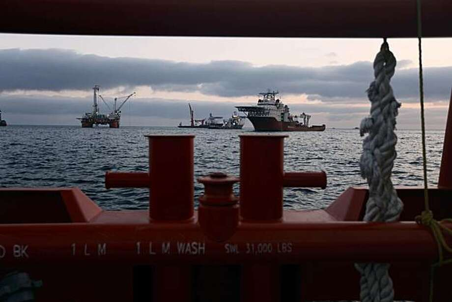 The Q4000, left, which has lowered the containment device to the sea floor, is seen in the early morning light with other support vessels from the deck of the Joe Griffin at the site of the Deepwater Horizon oil spill containment efforts in the Gulf of Mexico off the coast of Louisiana Saturday, May 8, 2010. Photo: Gerald Herbert, AP