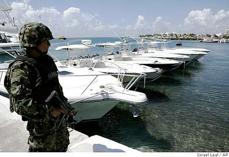 A Navy sailor guards Florida speed boats seized in Isla Mujeres off the Caribbean coast of Mexico, Monday, Oct. 6, 2008. The boats were allegedly used to smuggle Cubans to Mexico, a route used by more than 11,000 Cuban migrants to reach the US last year. (AP Photo/Israel Leal) Photo: Israel Leal, AP