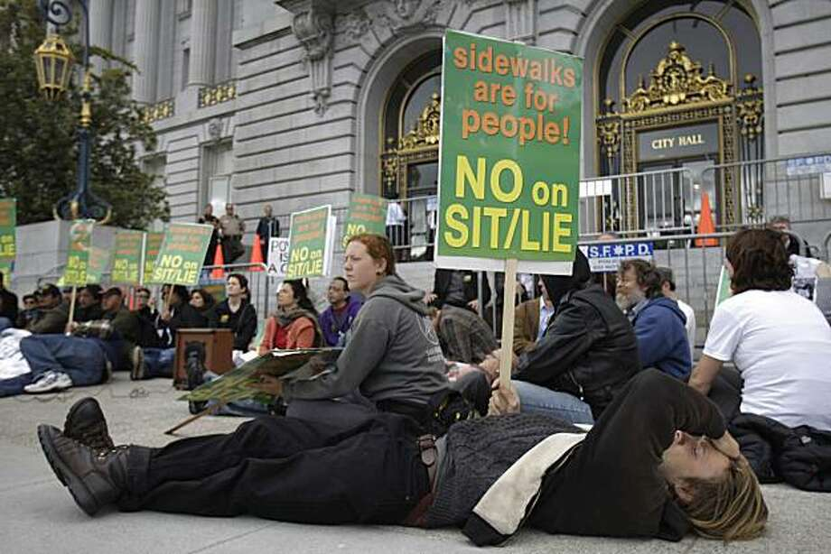 Shane (foreground) of San Francisco lays on the sidewalk in front of City Hall with other protesters to protest the proposed ordinance that would make it a crime to sit or lie on public sidewalks in San Francisco at City Hall in San Francisco, Calif. on Monday May 10, 2010. Photo: Lea Suzuki, The Chronicle