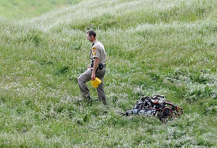 A Contra Costa County Sheriff deputy walks past the engine of a Piper Cherokee that crashed southeast of Mount Diablo State Park along Morgan Territory Road on Sunday, May 9, 2010 in Contra Costa County, Calif. Authorities say the two people on board thesmall plane heading for San Carlos Airport are dead after their plane crashed near Livermore Airport. Photo: Jose Carlos Fajardo, AP