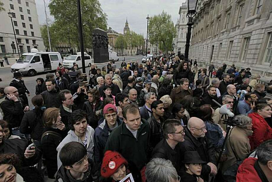 Members of the public gather outside the Cabinet Office where Britain's Conservative Party representatives were meeting with representatives of the Liberal Democrats party, in central London, Sunday May 9, 2010. Senior party leaders from Britain's first-place Conservatives and third-place Liberal Democrats are in talks about whether the two parties can work together to form a new government after an election that failed to produce a clear winner. Photo: Lefteris Pitarakis, AP