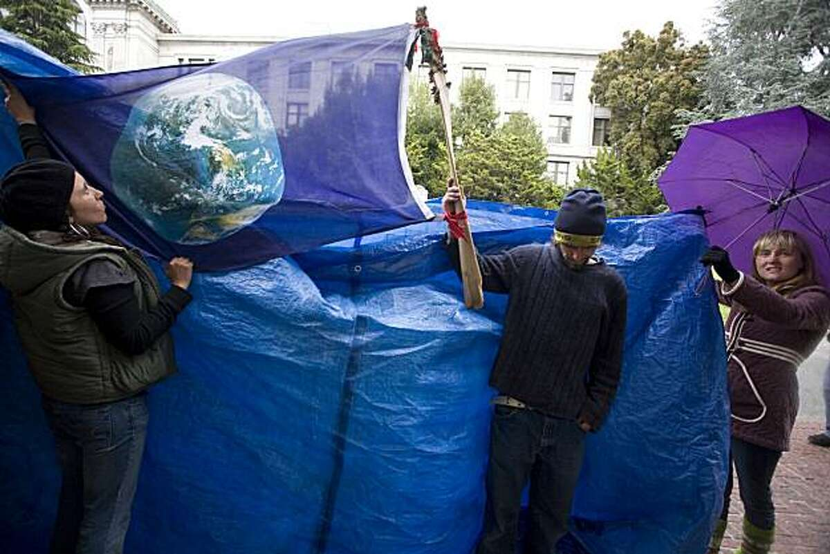 Student Marika Goodrich, left, and other protesters that prefer to remain anonymous, use a tarp, a world flag and an umbrella to block campus police from filming hunger strikers as they hang a sign reading