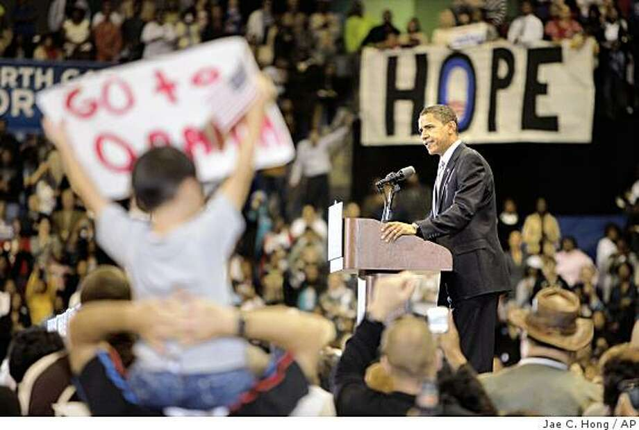 A boy holds up a sign supporting Democratic presidential candidate, Sen. Barack Obama, D-Ill., right, at a rally in Fayetteville, N.C., Sunday, Oct. 19, 2008. (AP Photo/Jae C. Hong) Photo: Jae C. Hong, AP