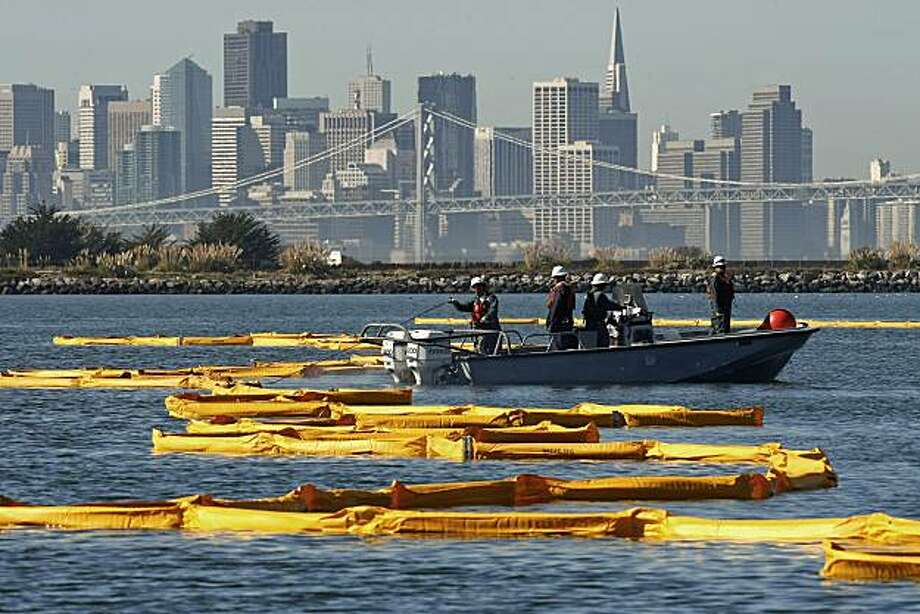 "Personnel with NRC Environmental Services deploy containment booms near their offices on the former Alameda Naval Air Station, in response  to an oil spill in San Francisco Bay, after the ship, ""Dubai Star"" spilled bunker fuel into the water south of the Bay Bridge near Alameda, Calif, on Friday October 30, 2009. Photo: Michael Macor, The Chronicle"