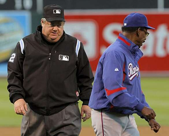 Umpire Joe West looks at Rangers manager Ron Washington after Washington reacted to being tossed from the game in the bottom of the second inning for arguing a call in Oakland on Monday. Photo: Carlos Avila Gonzalez, The Chronicle