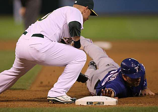 OAKLAND, CA - MAY 3: Matt Treanor #15 of the Texas Rangers is tagged out at first on a pick off attempt in the fifth inning by Daric Barton #10 of the Oakland Athletics during an MLB game at the Oakland-Alameda County Coliseum on May 3, 2010 in Oakland, California. Photo: Jed Jacobsohn, Getty Images