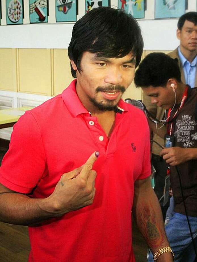 Philippine boxing hero Manny Pacquiao (L) shows his finger marked with indelible ink after casting his vote at a polling center in Kiamba, Sarangani province, in the southern island of Mindanao on May 10, 2010. Ten people were killed and glitches with vote-counting machines frustrated voters in Philippine elections, but authorities insisted the country's first automated ballot was a success. Photo: Mark Navales, AFP/Getty Images