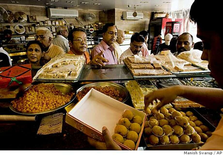 "**APN ADVANCE FOR SUNDAY OCT. 12**  People buy sweets ahead of festival seasons from a sweet shop, in New Delhi, India, Tuesday, Sept. 30, 2008. For thousands of years food for the Diwali festival meant just one thing _ sweets, sweets and more sweets. These ""mithai"" _ gorgeous, sugary fudge-like sweets, flavored with cardamon, cashews, pistachio and saffron and often coated in a pure silver foil beaten so thin it melts in the mouth _ have been central to the celebrations of the Hindu festival of lights, greedily eaten, given as gifts and offered to the gods. (AP Photo/Manish Swarup) Photo: Manish Swarup, AP"