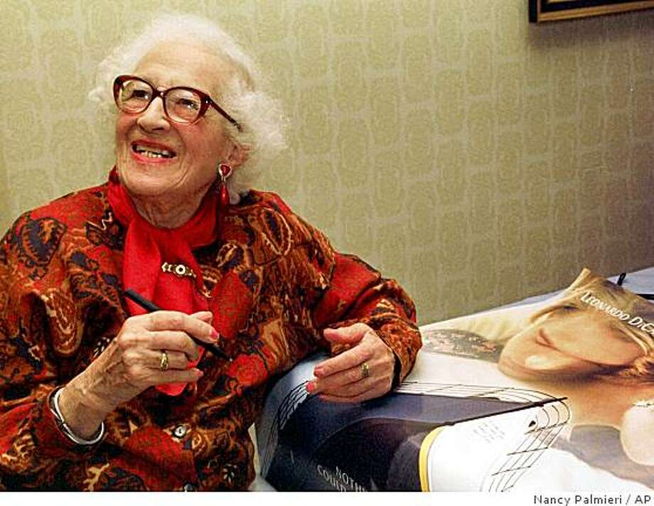 ** FILE  **  This is a Friday, April 17, 1998 file photo of Millvina Dean, 86, a living Titanic survivor, as she  looks up and smiles as she signs a Titanic movie poster for an enthusiast at the Titanic Historical Society's convention in Springfield, Mass. As a 2-month-old baby, Millvina Dean was wrapped in a sack and lowered into a lifeboat from the deck of the sinking RMS Titanic.  Now Dean, the last living survivor of the disaster, is selling some of her mementos to help pay her nursing home fees. Dean's artifacts, including a suitcase given to her family by the people of New York after their rescue, are expected to sell for about 3,000 pounds (US$5,200) at Saturday's auction in Devizes, western England. Dean, 96, has lived in a nursing home in the southern English city of Southampton Titanic's home port  since she broke her hip two years ago. (AP Photo/Nancy Palmieri) Photo: Nancy Palmieri, AP