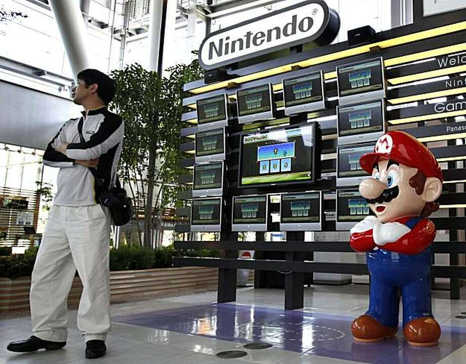 A man stands in front of Nintendo's game monitors in a showroom in Tokyo  Thursday, May 6, 2010. The maker of Super Mario and Pokemon games said Thursday its net profit for the fiscal year ended March 31 fell 18 percent to 228.6 billion yen (US$2.5 billion). Photo: Shizuo Kambayashi, AP