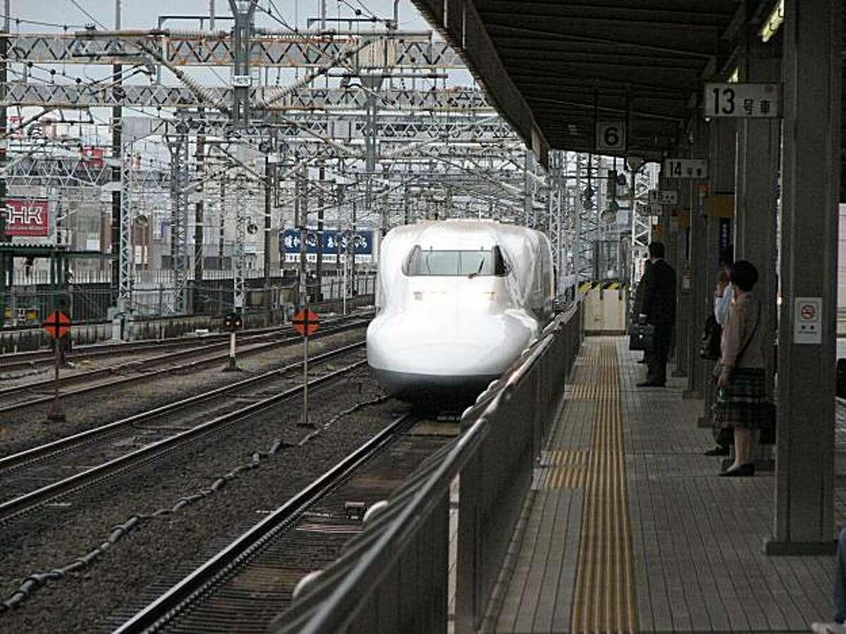 A Shinkansen high-speed train approaches a Tokyo station.
