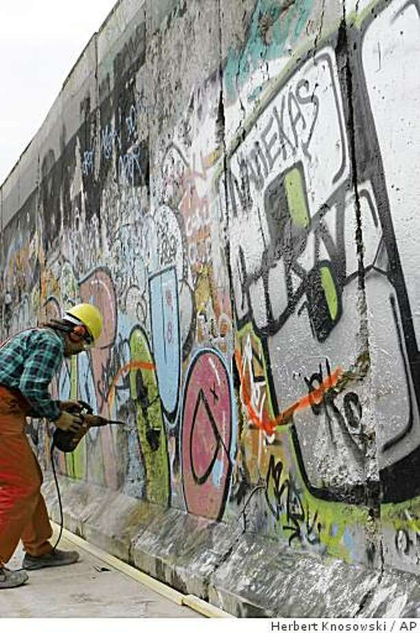 A worker starts renovation works at the East Side Gallery in Berlin, Germany, Wednesday, Oct. 15, 2008. The restoration of the 105 wall paintings, remains of former Berlin Wall, is scheduled to be finished for the 20th anniversary of the opening of the Berlin Wall in November 2009. The same 118 artists from 21 countries who created the paintings in 1990 will repaint their pictures after replacement of the concrete surface of the Wall. (AP Photo/Herbert Knosowski) Photo: Herbert Knosowski, AP