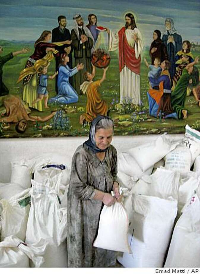 Iraqi Christian woman carries a sack of humanitarian aid inside a Chaldean nunnery where many  Christian families took refuge, in the village of Karaqoush, 28 kilometers (20 miles)  east of Mosul, Thursday, Oct. 16, 2008. An Iraqi official said Thursday that the number of Christian families fleeing violence in the northern city of Mosul since last week has reached over 8,300 people.Islamic extremists have frequently targeted Christians and other religious minorities since the 2003 U.S. invasion, forcing tens of thousands to flee Iraq. (AP Photo/Emad Matti) Photo: Emad Matti, AP