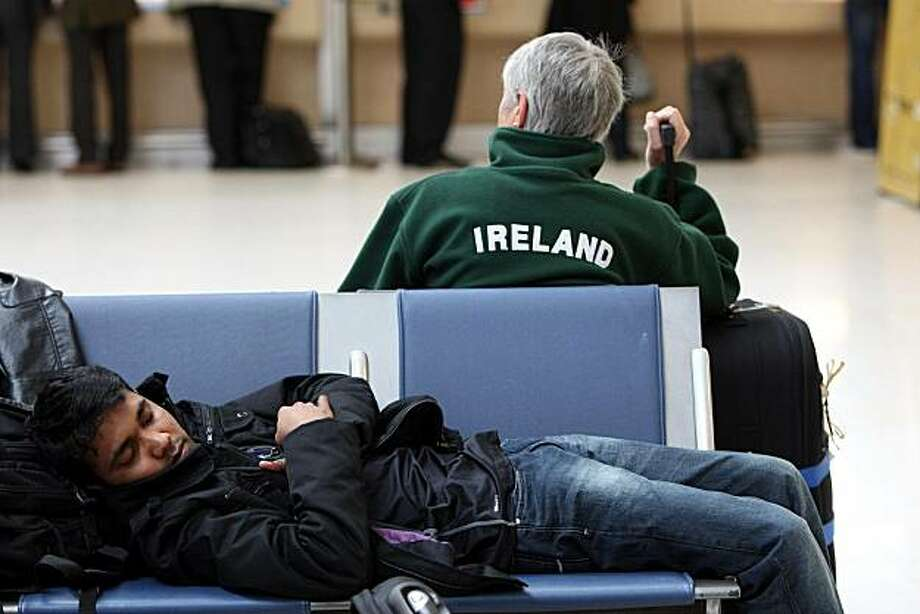 **  CORRECTS THE LOCATION OF AIRPORT ** A passenger takes a nap in the flight departures area of Belfast City airport, as the return of the Icelandic volcanic ash cloud caused travel misery for thousands of air passengers with hundreds of flights canceledTuesday May 4, 2010. Airlines had to scrap all services to and from the Republic of Ireland and Northern Ireland after no-flight restrictions were introduced until 1pm. Photo: AP