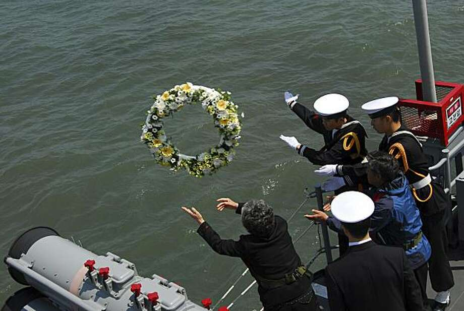In this photo released by the South Korea Navy via Yonhap, family members of the deceased sailors from the sunken South Korean naval ship Cheonan throw flowers from a naval ship as they visit the site in the waters off the Baengnyeong Island, South Korea,Friday, April 30, 2010. The Cheonan was on a routine patrol mission in the waters near the Koreas' maritime border when an explosion ripped the sturdy frigate in two. Fifty-eight sailors were rescued; 46 others perished. Photo: AP