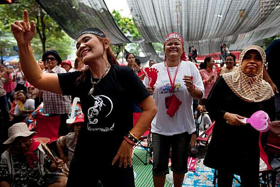 """BANGKOK, THAILAND - MAY 4:  Anti-government protesters or """"Red shirts"""" enjoy speeches as leaders discuss the reconciliation process May 4, 2010 in Bangkok, Thailand. Prime Minister Abhisit Vejjajiva came out with a 5 step roadmap peace proposal to end Thailand's eight weeks of political crisis. For now the red shirts say they will stay on the streets, continuing the process of negotiations. The anti-government protests that have closed much of central Bangkok's commercial district. Photo: Paula Bronstein, Getty Images"""
