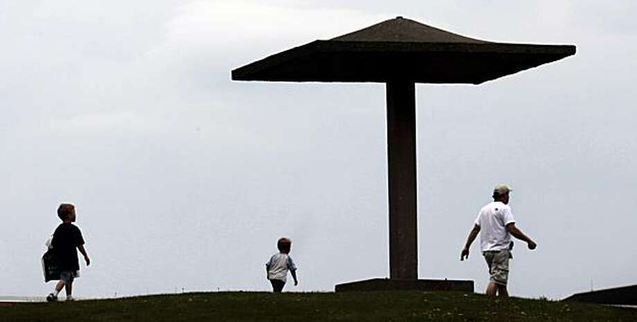 A father and his sons walk by the pagoda on the campus of Kent State University in Kent,  Ohio on Saturday, May 1,  2010.  On May 4, 1970, National Guard troops stood at this pagoda a fired into a crowd of students, killing four and wounding nine others during a Vietnam era protest on the campus.  May 4, 2010 marks the 40th anniversary of the incident. Photo: Amy Sancetta, AP