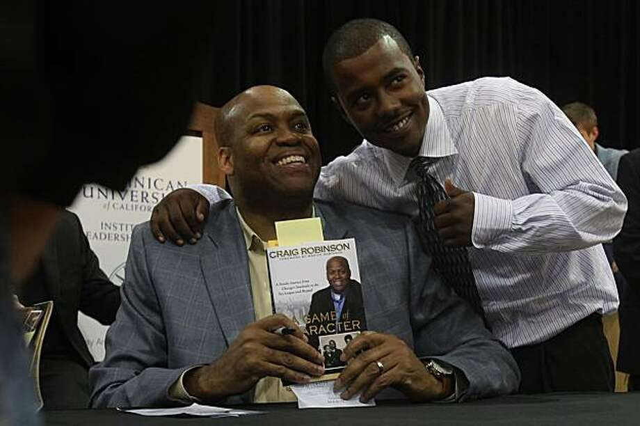 """Craig Robinson, Michelle Obama's brother, poses with Joshua Green, 19 years old, during a book signing after Robinson speaks about his book, """"A Game of Character"""" at Dominican College in San Rafael, Calif.,  on Tuesday, April 27, 2010. Photo: Liz Hafalia, The Chronicle"""
