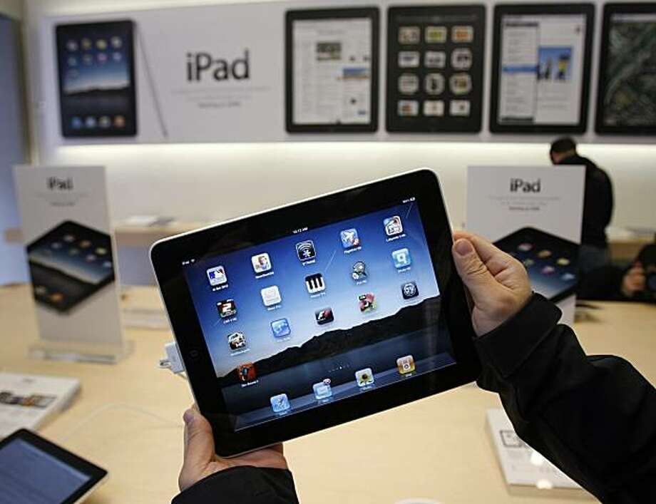 FILE - In this April 3, 2010 file photo showing customer uses an Apple iPad on the first day of Apple iPad sales at an Apple store in San Francisco. Apple said Monday, May 3, 2010, it has sold 1 million of its new iPad tablet computers in the month afterits launch, meaning it's been selling more than twice as fast as the iPhone did when it was new. Photo: Paul Sakuma, AP