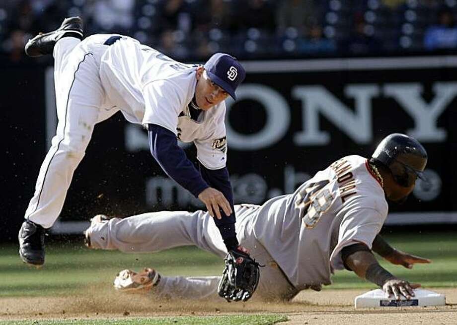 San Diego Padres second baseman David Eckstein, left, avoids the sweeping slide of San Francisco Giants' Pablo Sandoval while relaying to first to complete a double play in the fourth inning of the Padres' 5-2 victory in a baseball game Wednesday, April 21, 2010, in San Diego. Photo: Lenny Ignelzi, AP