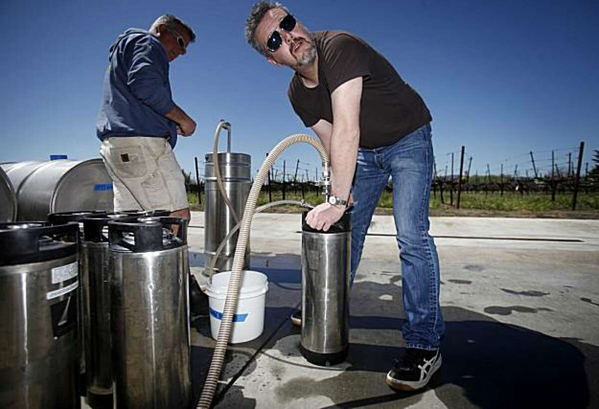 """With the help of Abe Schoener (left), wine maker at Tenbrink Winery, Gus Vahlkamp, wine director for """"Out The Door,"""" fills one of his kegs at Tenbrink Winery with a new supply of wine on Wednesday April 4, 2010 in Fairfield, Calif."""