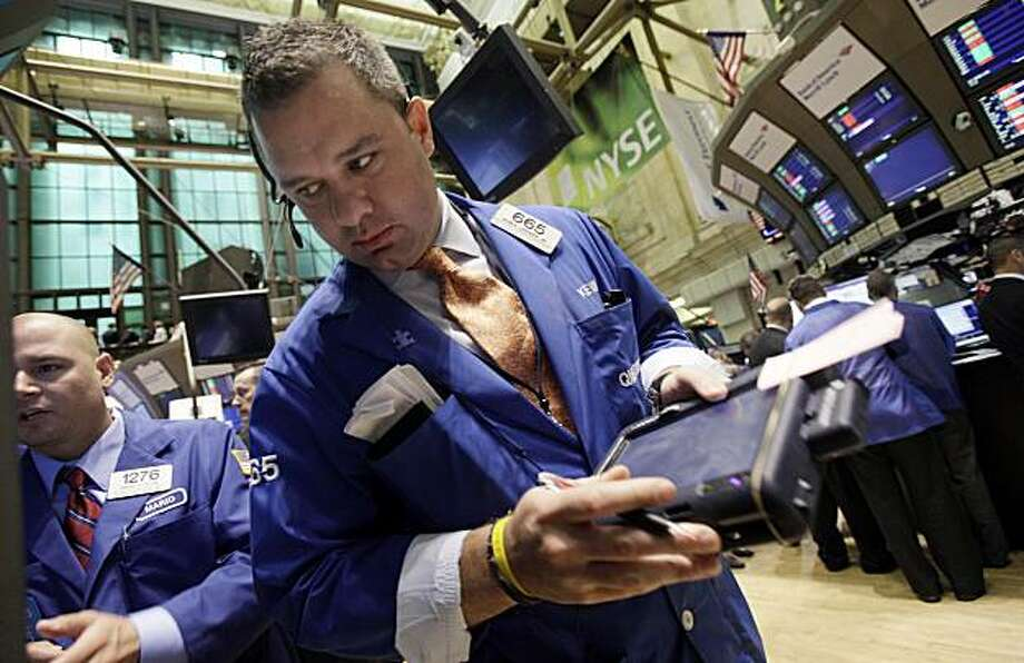 Trader Kevin Lodewick Jr., right, works  on the floor of the New York Stock Exchange Wednesday, May 5, 2010. Photo: Richard Drew, AP