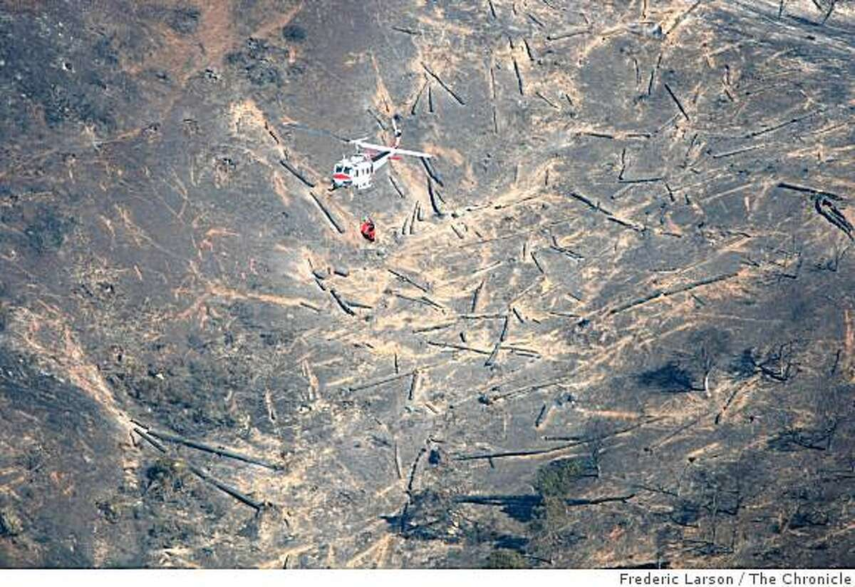 A helicopter being used to fight the Angel Island fire is seen over a burned portion of the Island on Monday.