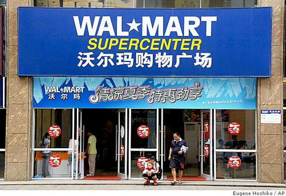 ** ADVANCE FOR SUNDAY, OCT. 19 ** Customers walk out from the gate of Wal-Mart supermarket in Loudi,  Hunan Province, China Friday June 20, 2008. Maoming, Wuhu and Loudi are Chinese cities so far in the boonies that the popular Lonely Planet travel guide doesn't even mention them, but Wal-Mart has found them. The American mega-retailer is making an aggressive push into China's smaller markets as economic growth spreads to the hinterlands. The expansion is a key part of Wal-Mart's attempt to gain a bigger foothold in what could become the world's largest retail market. (AP Photo/Eugene Hoshiko) ** NO ONLN ** NO IONLN ** Photo: Eugene Hoshiko, AP