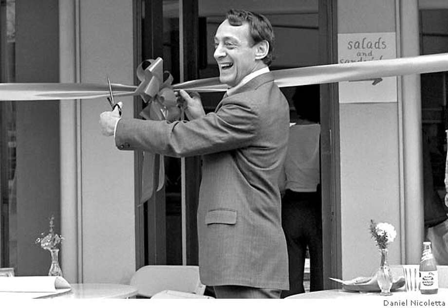 "Possible caption - feel free to paraphrase: At the dedication of One United Nations Plaza Cafe in SF, never one to miss an opportunity to use the press and humor to illustrate his openly gay identity, Supervisor Harvey Milk quipped ' i am probably the only elected official who cuts the ribbon and then puts it in his hair"" Mar. 7, 1978 Photo: Photo By Daniel Nicoletta"